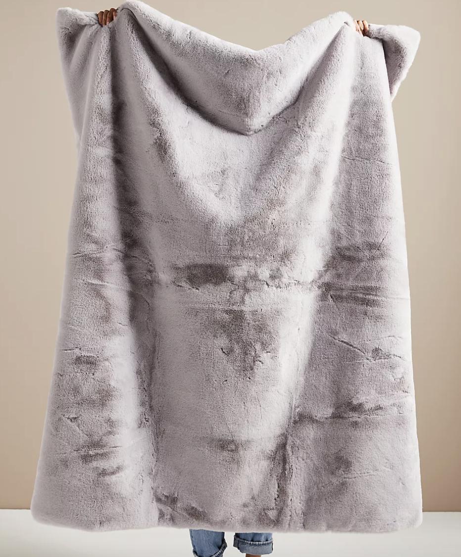 Model holding up gray faux fur blanket