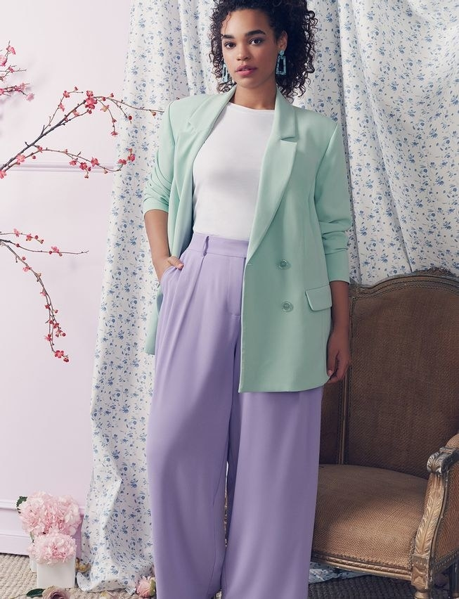 model wearing the blazer in a mint color with wide-leg pants