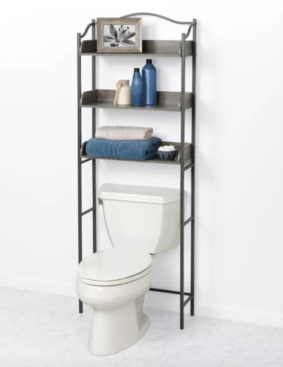 brown storage unit with three shelves above white toilet