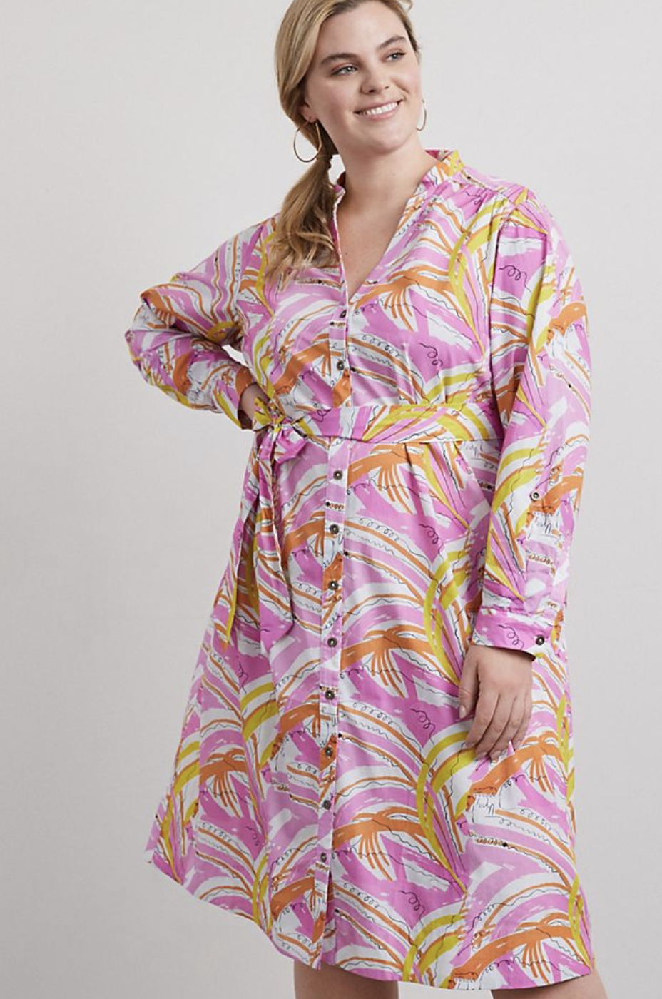 Model in button down long sleeved dress with orange and yellow trees printed on it