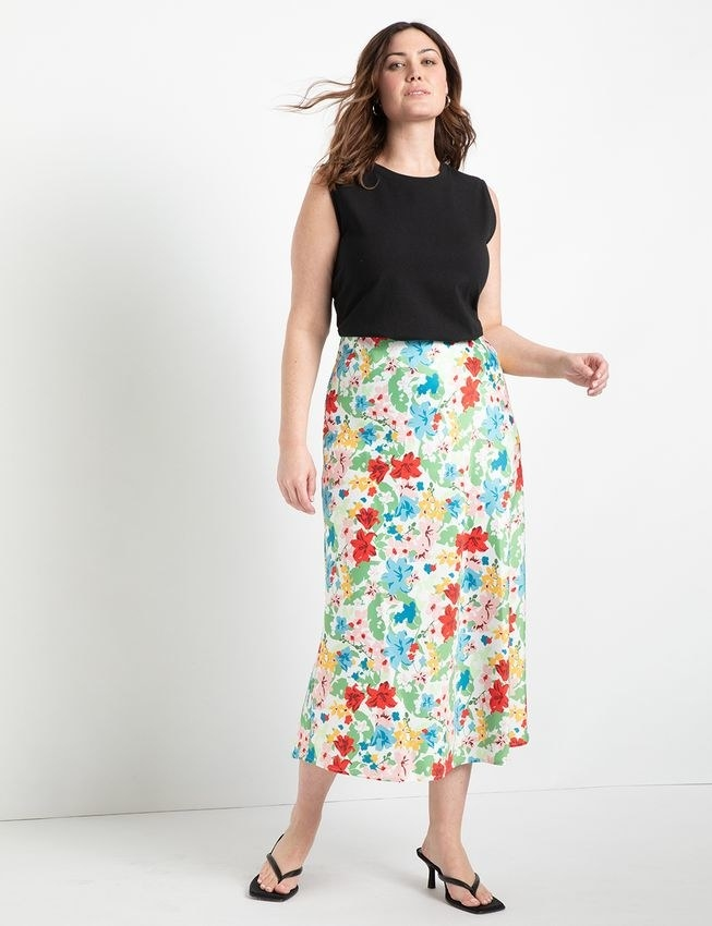 model wearing the floral satin skirt with a black tank and heels