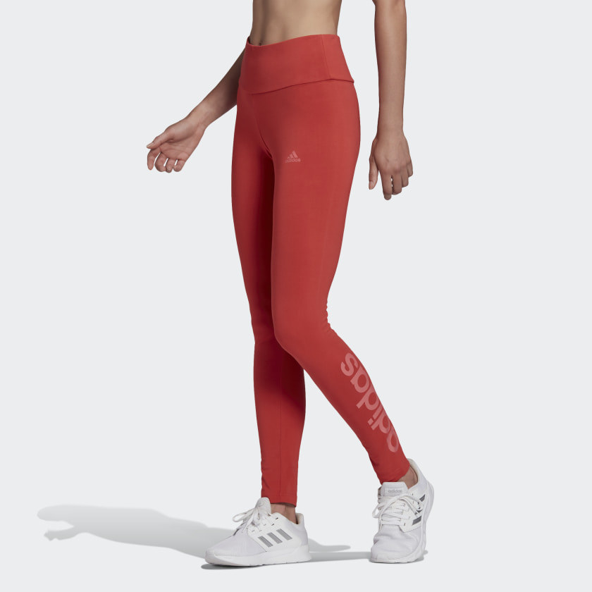 Model in a pair of red leggings that say Adidas on the side of the calf