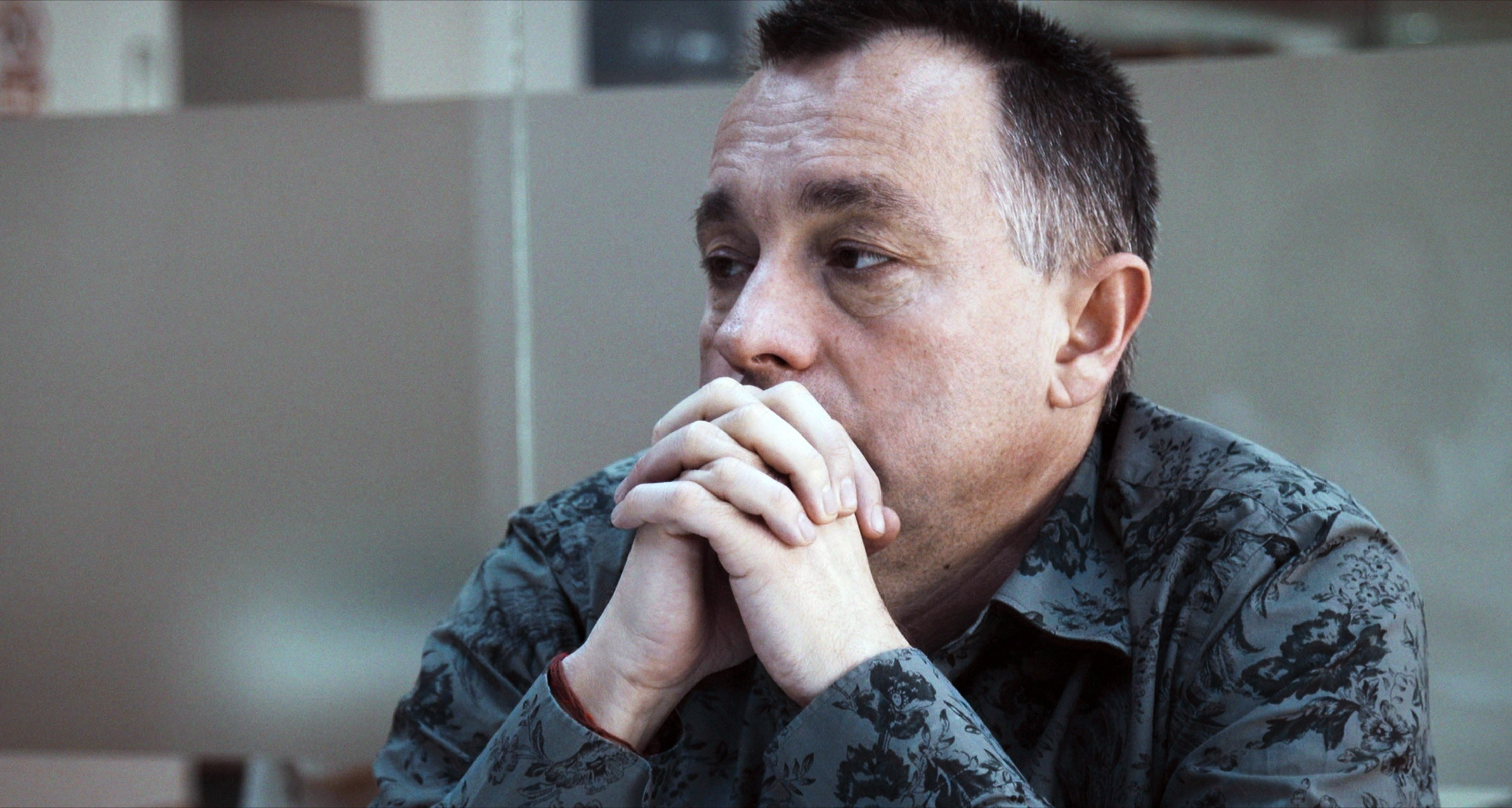 Sad-looking man sits with his hands clasped in front of his face