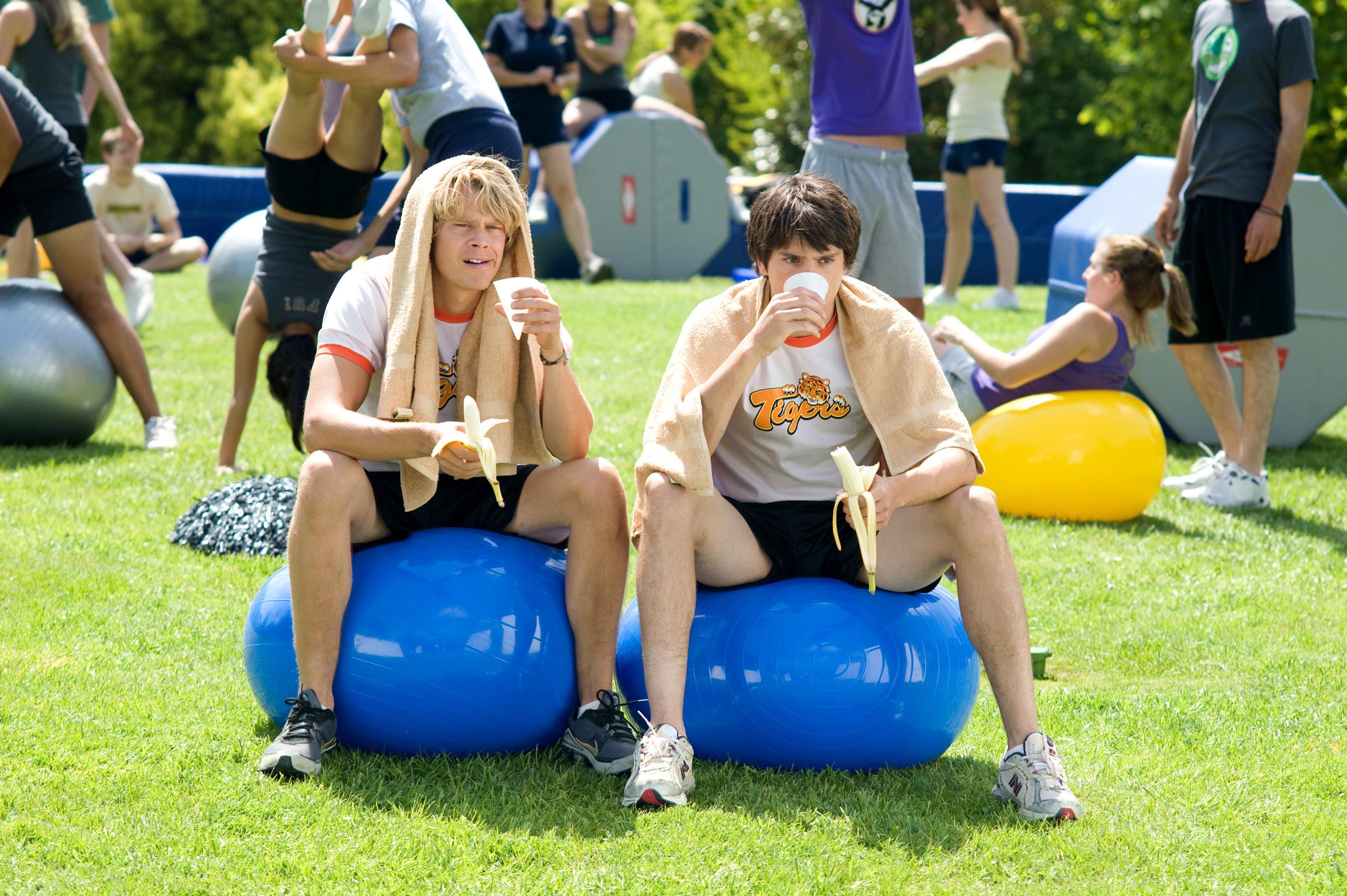 Eric Christian Olsen and Nicholas D'Agosto sitting on exercise balls