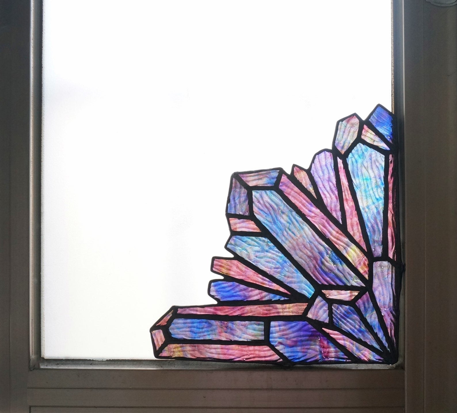 the iridescent glass crystal corner piece in the corner of a window