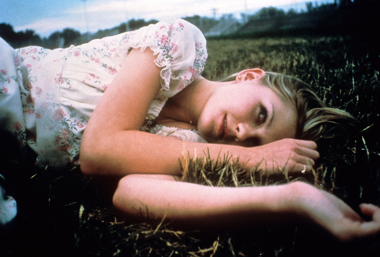 Kirsten Dunst lying in the grass