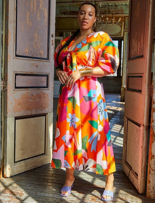 model wearing the bright multicolor dress with a tie-front and plunging neckline