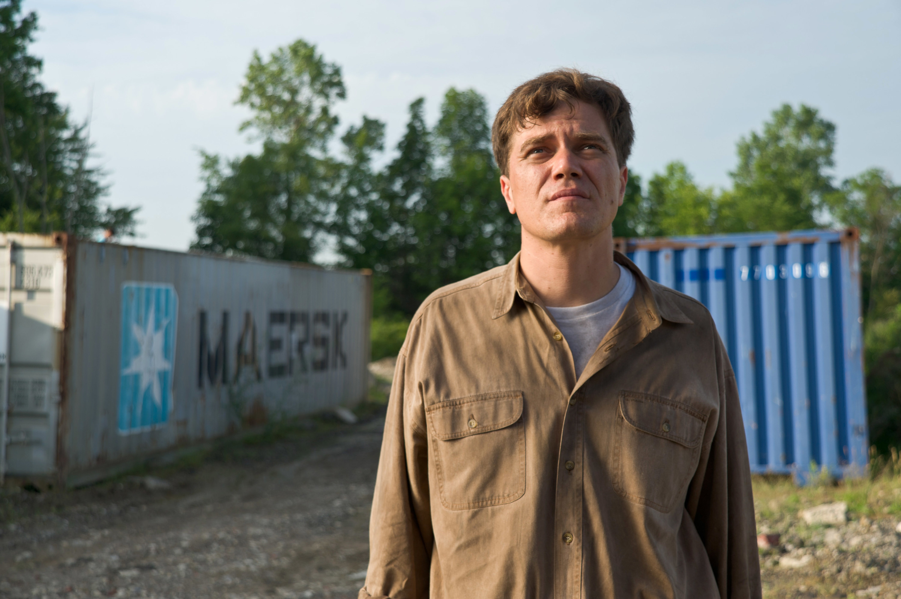 Michael Shannon standing outside and looking up