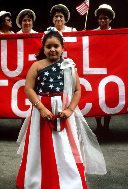 A young girl wearing a flag dress at a parade