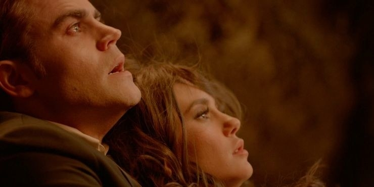 stefan holds a woman and they have their mouths slightly open, eyes wide as if scared