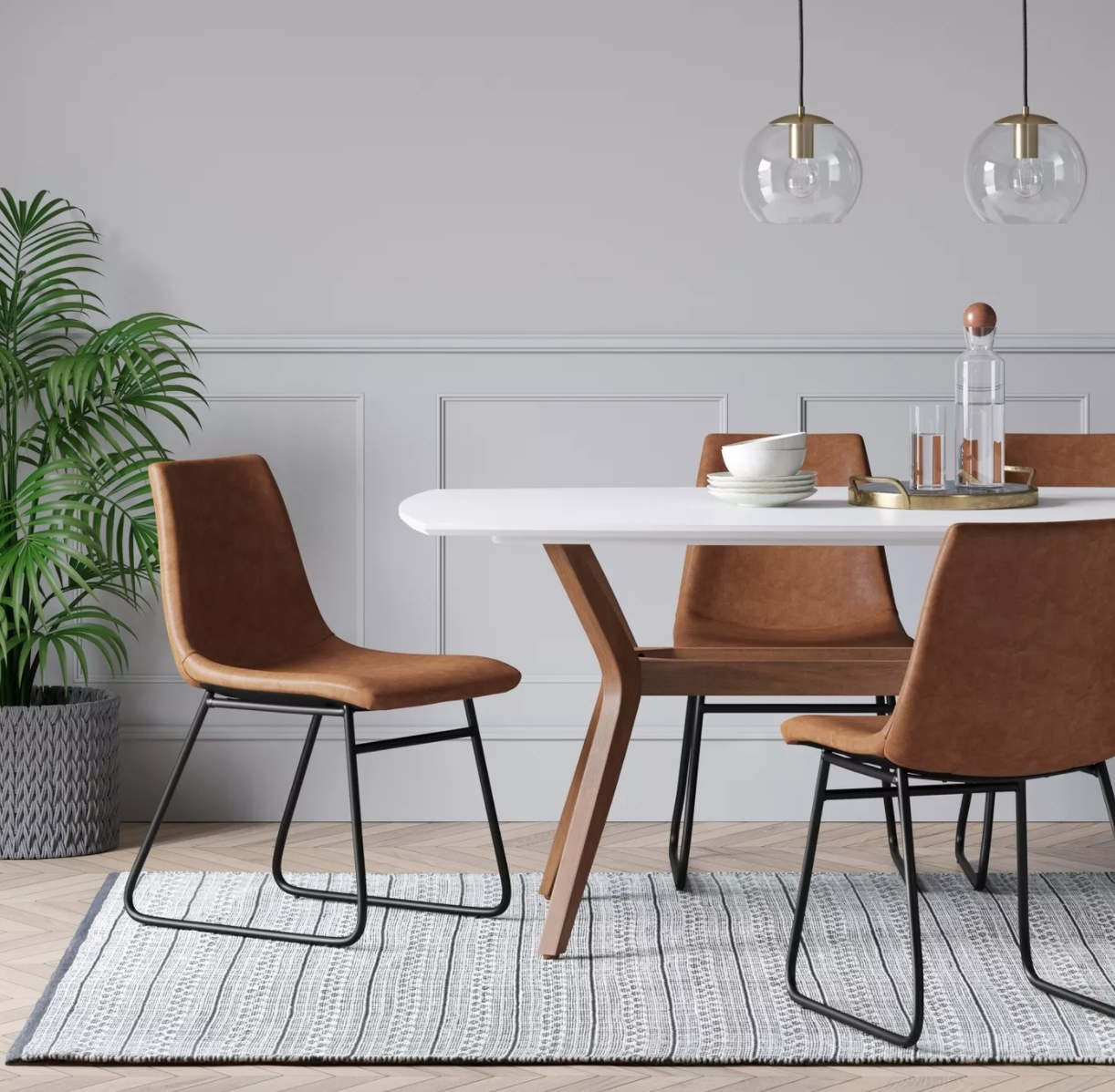 Four brown faux leather dining chairs with metal legs