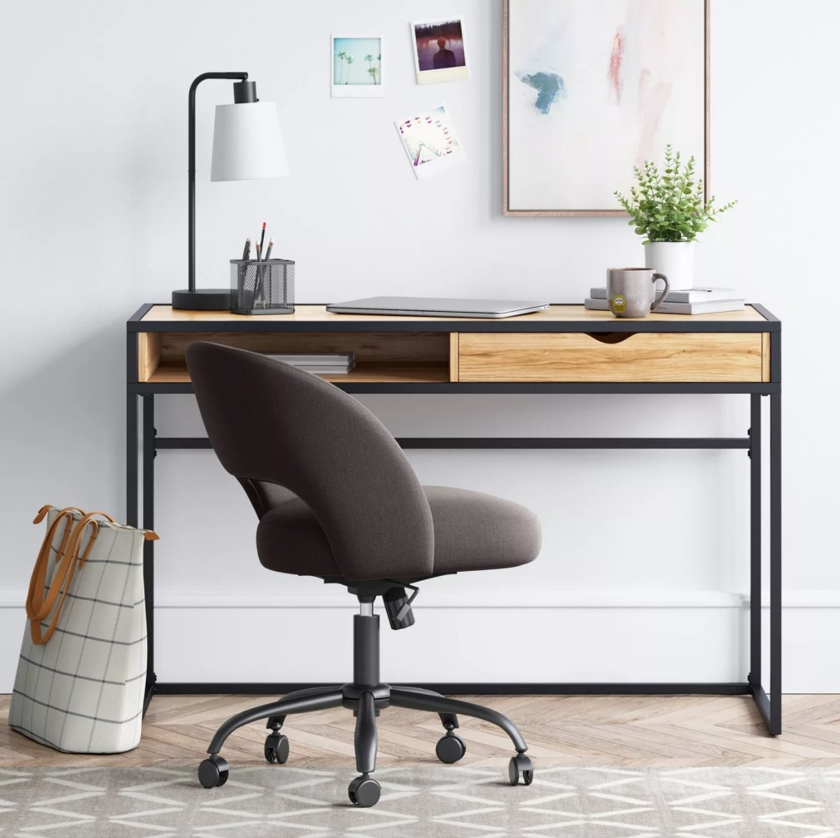 A gray upholstered desk chair with castor wheels and rounded back