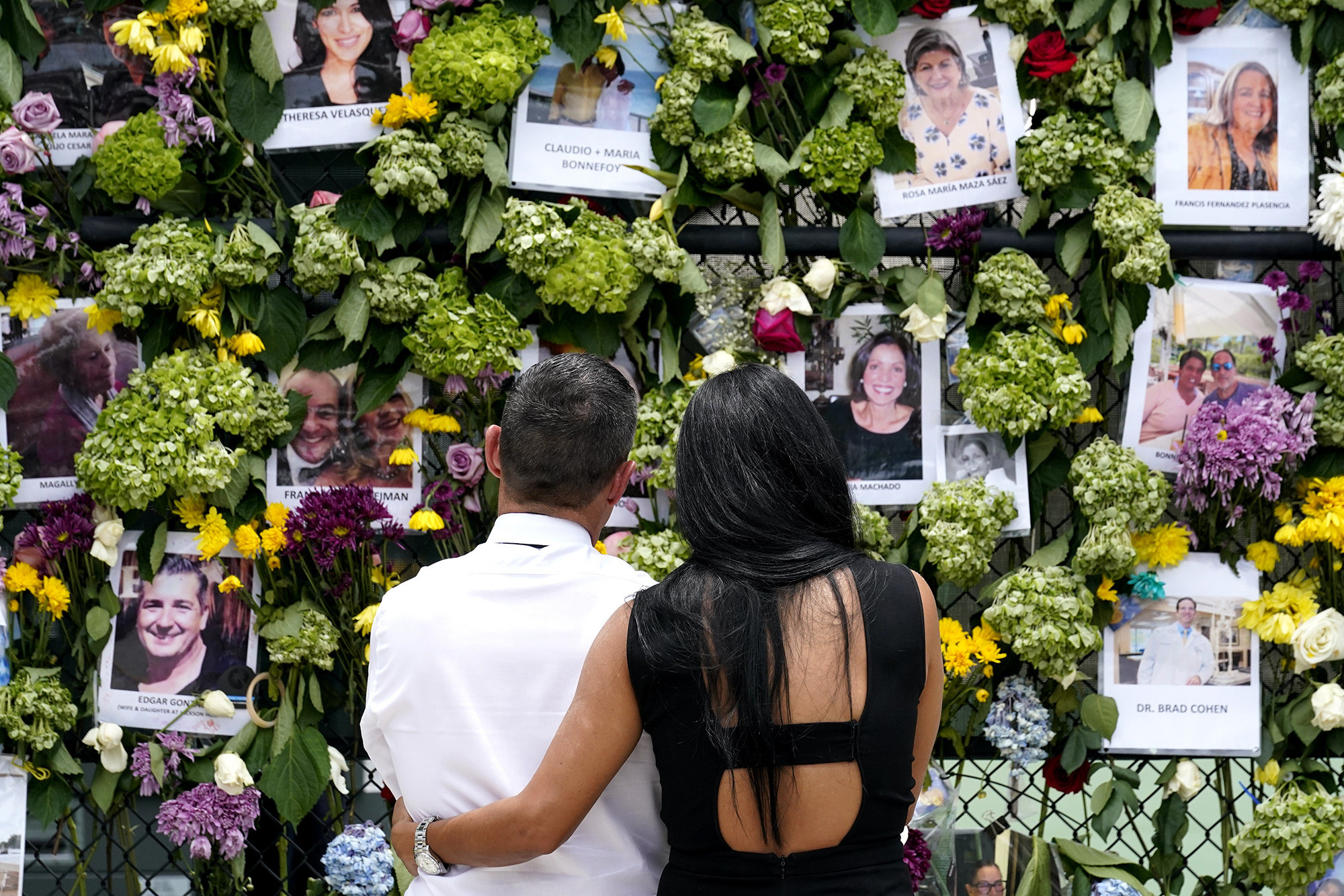 A couple embraces with their backs facing the camera, looking on at a photo memorial
