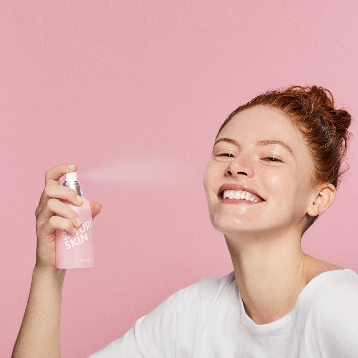 model spraying the bottle on her face