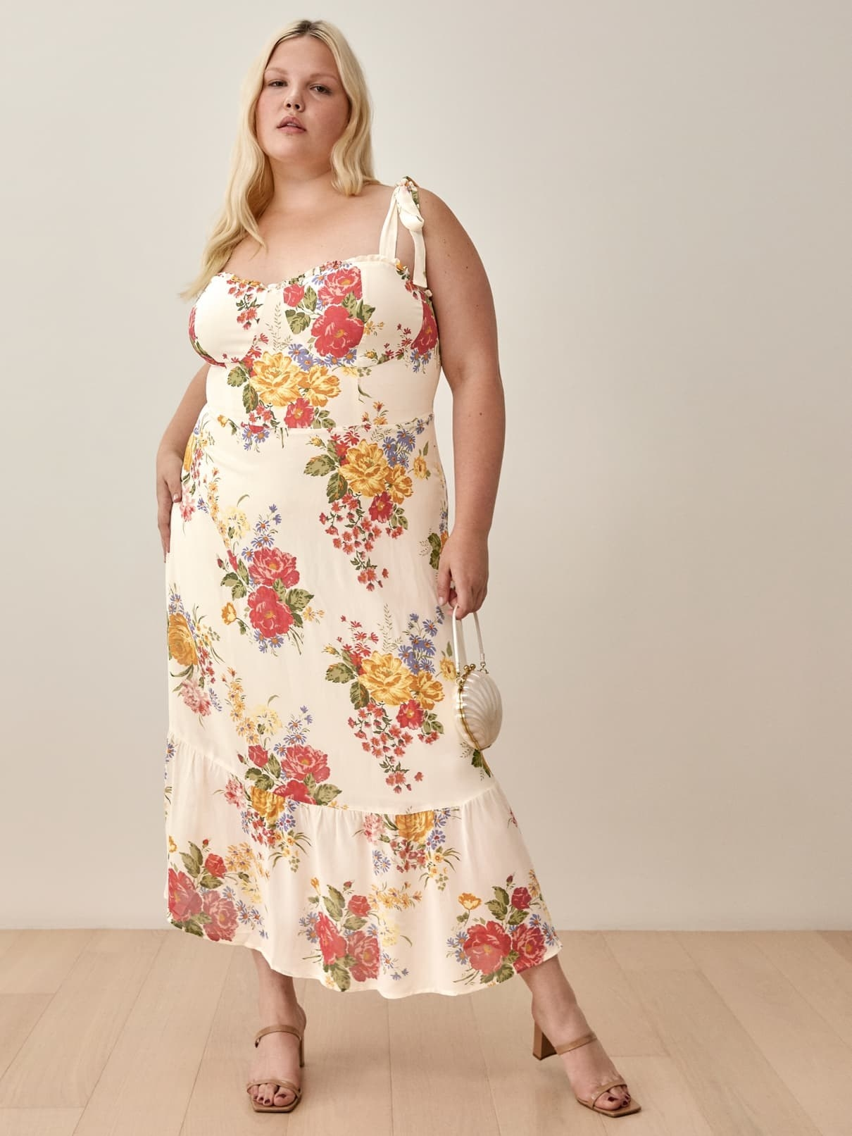 model wearing the cream colored dress with bouquet prints
