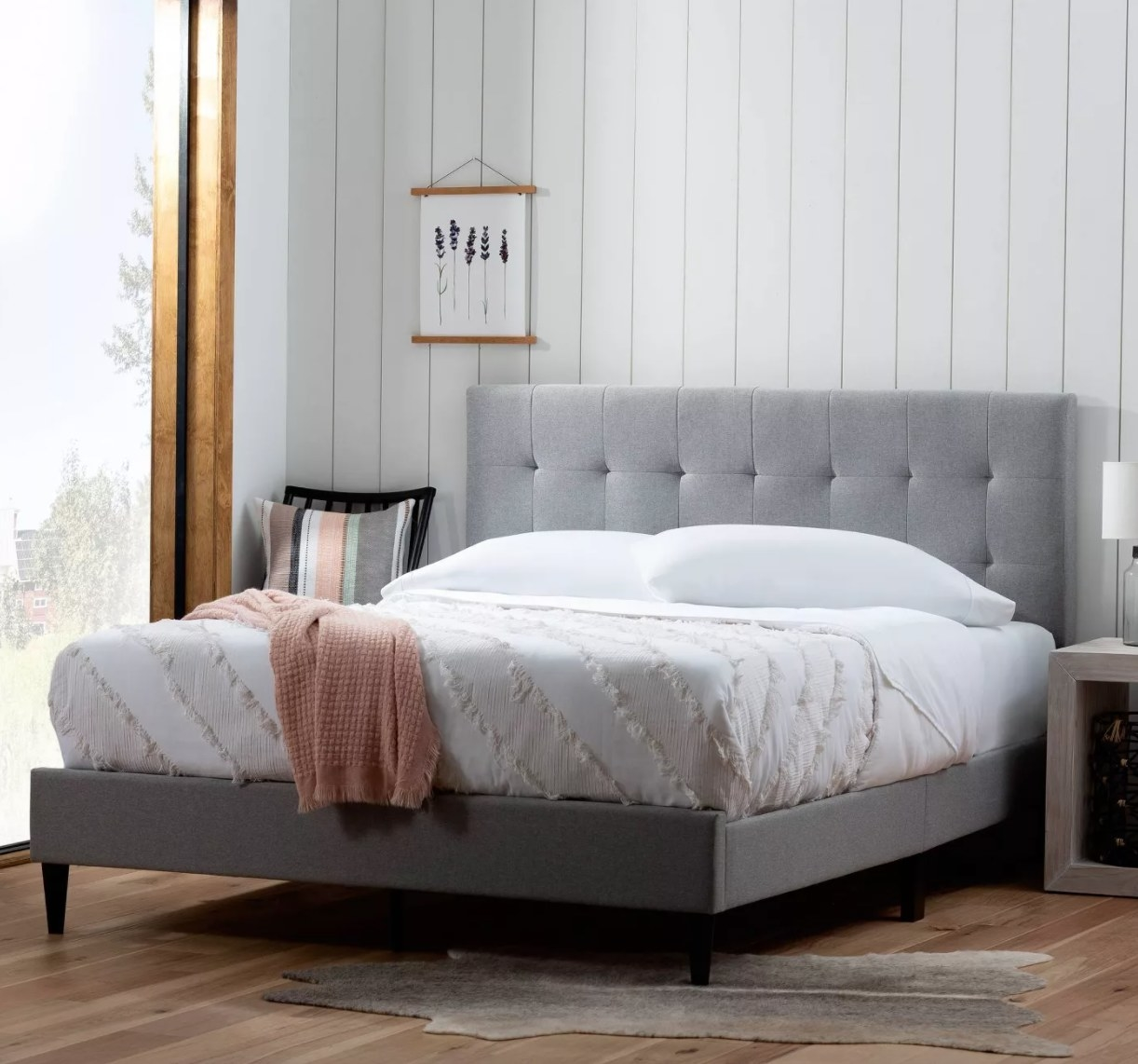 A light gray upholstered bed frame with tufted headboard