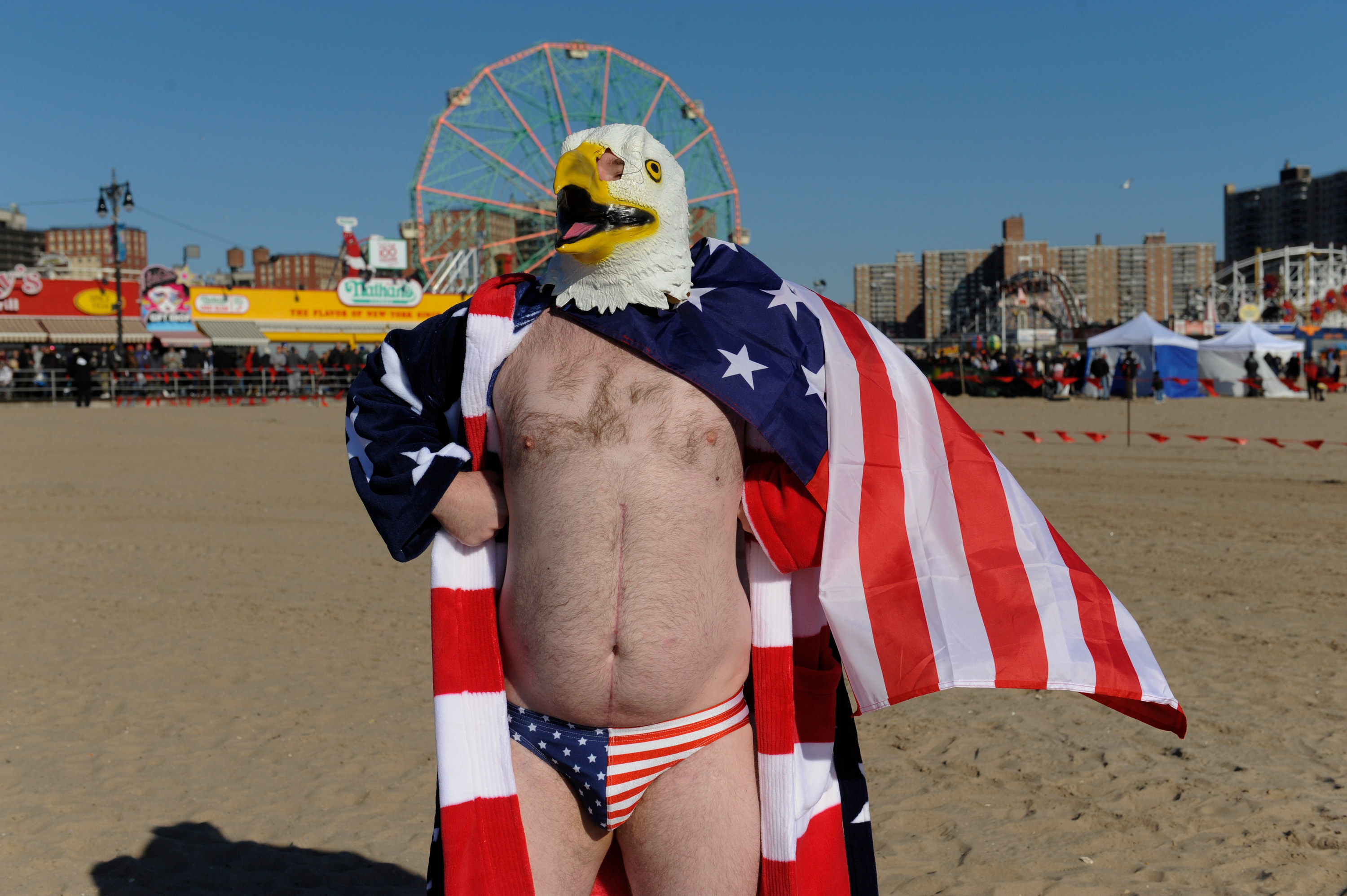 A man wearing a US flag Speedo and chicken head mask stands with a US flag draped over his shoulders