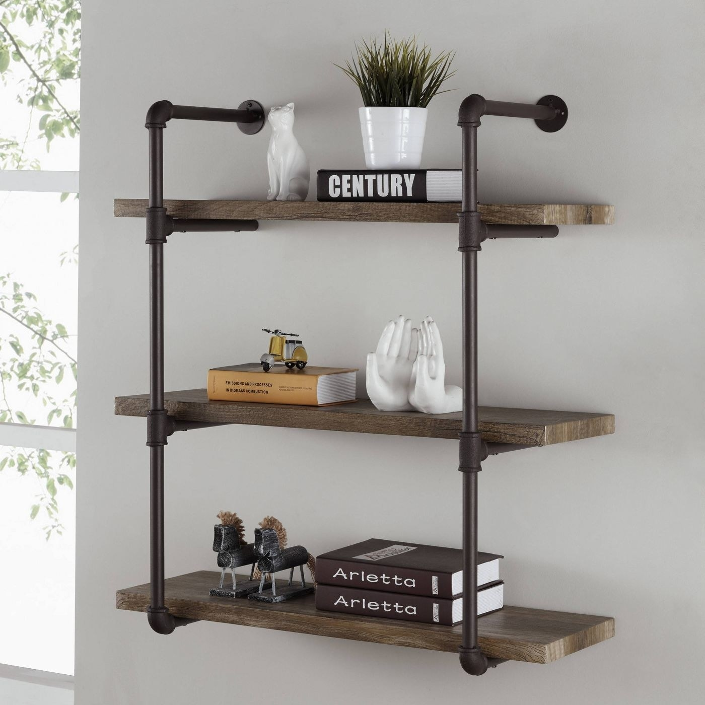 three wall shelves held together by industrial pipes
