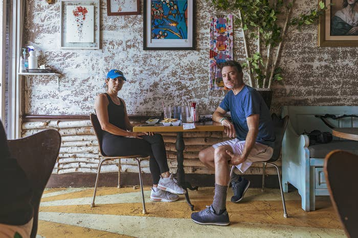 A couple in athletic clothes sit at a table with breakfast on it