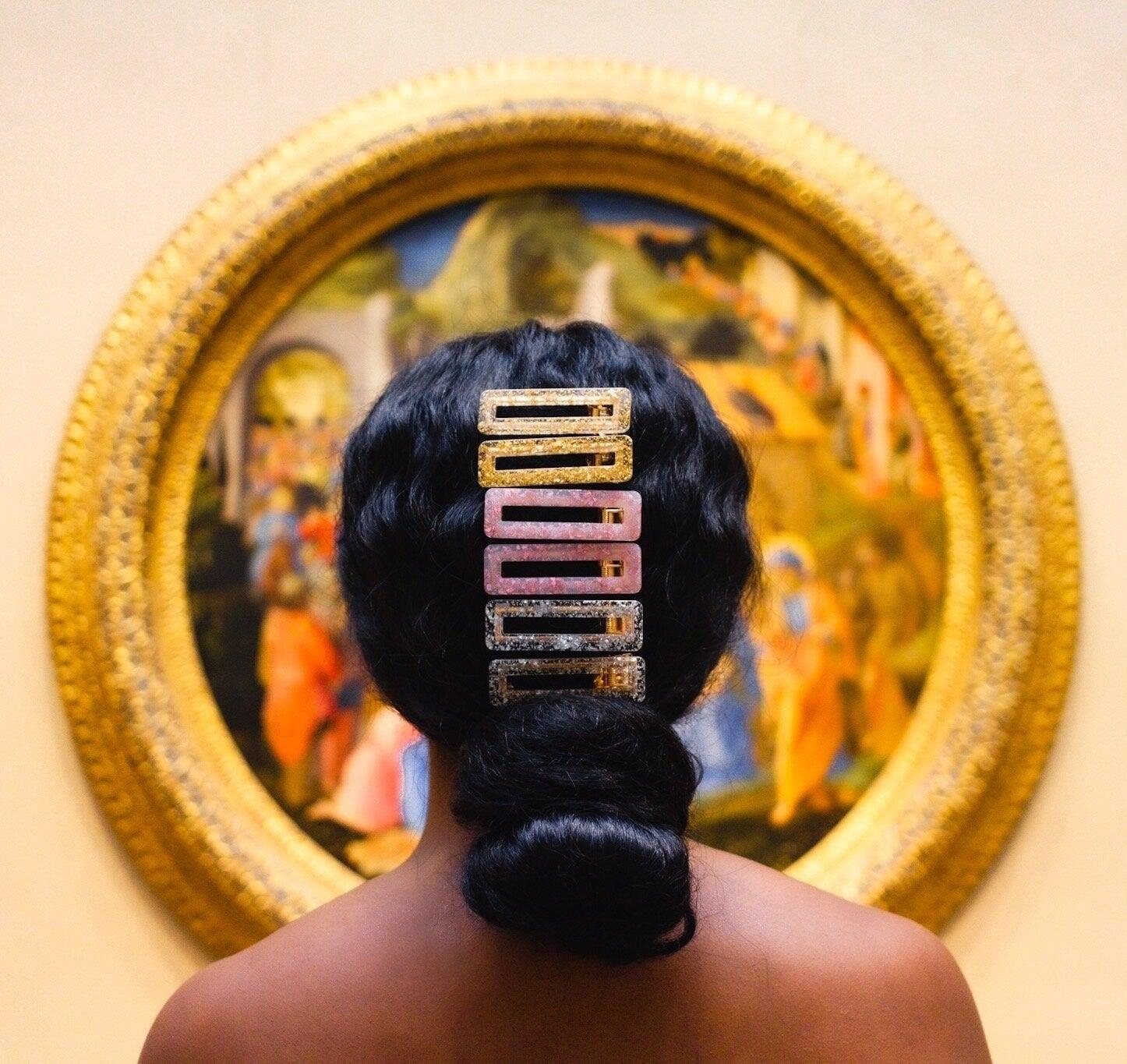 model wears multi-colored glittery hair clips in hair above low bun