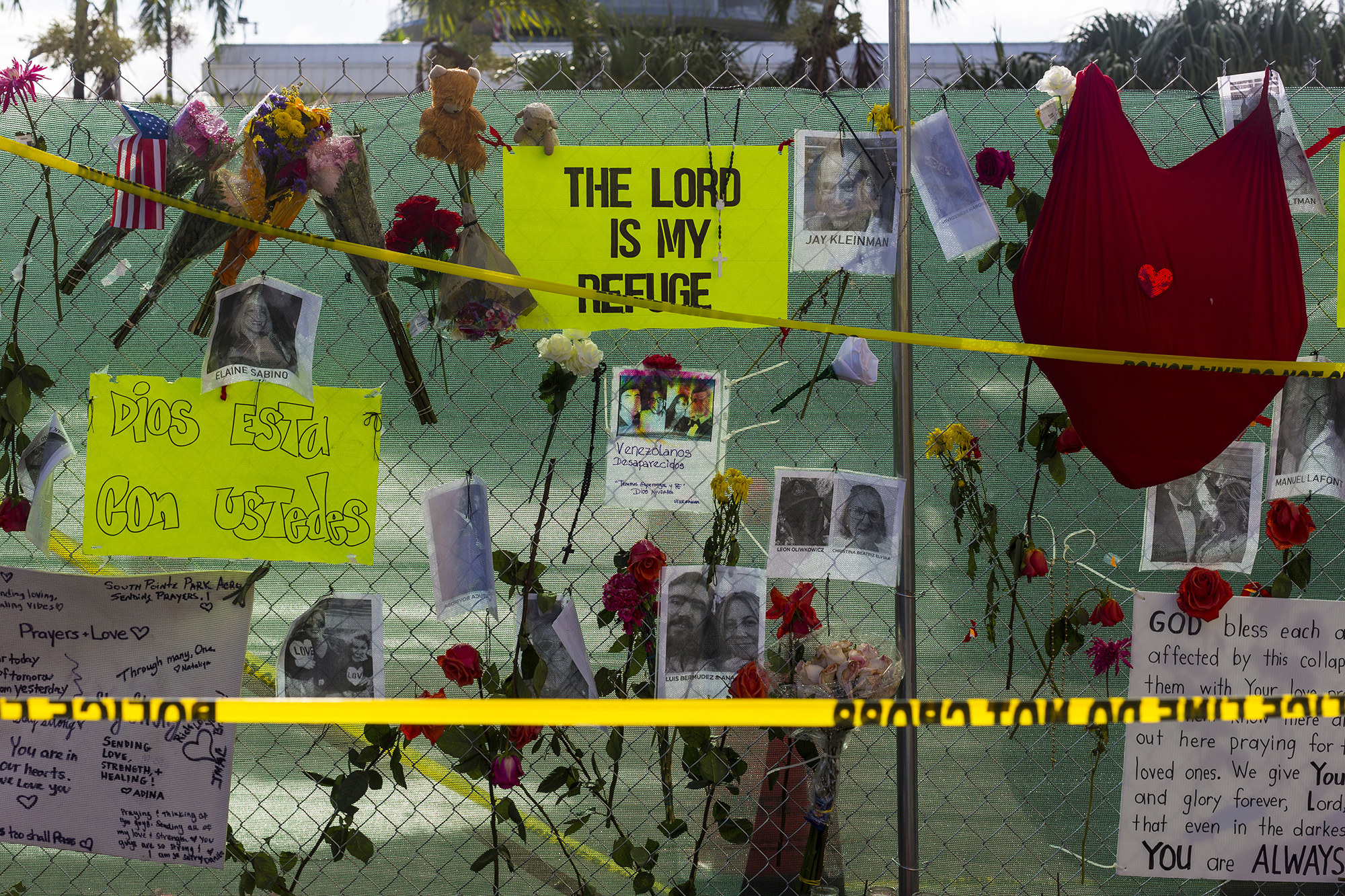 Flowers, posters and photos of people are shown behind police line tape