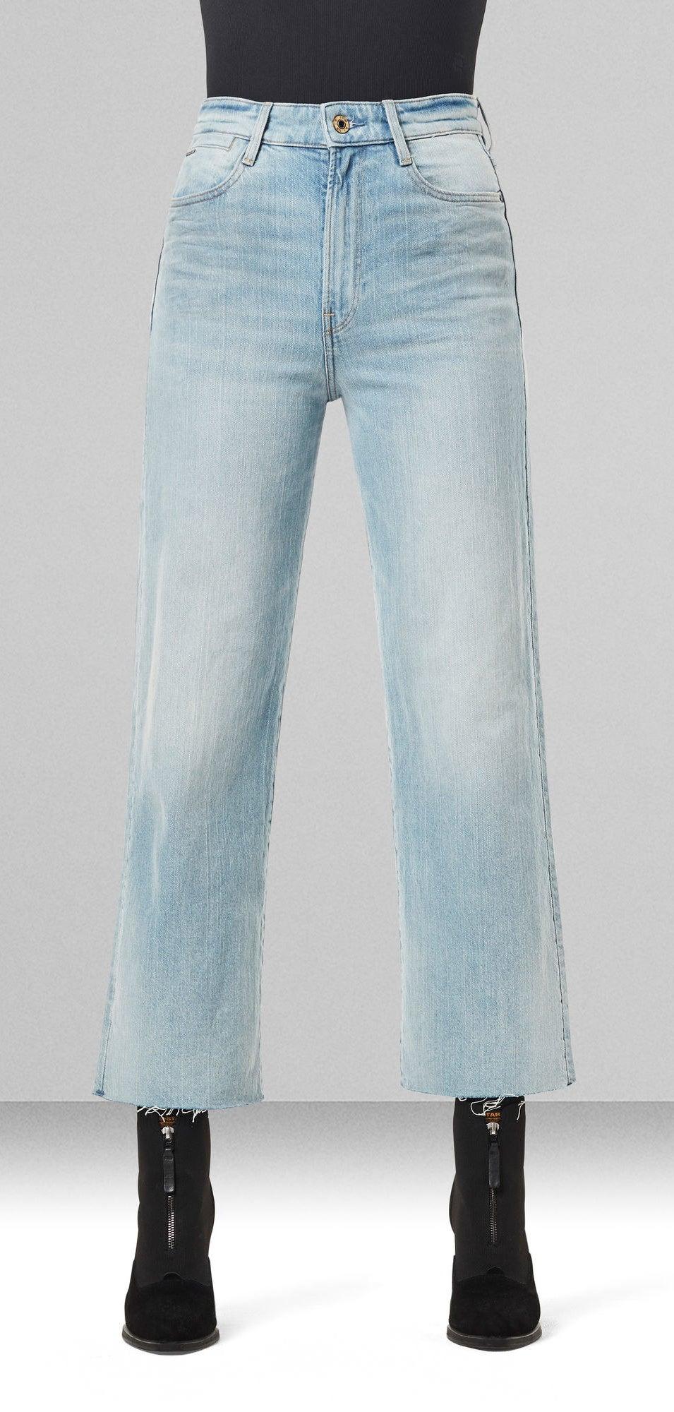 A model wears the pants in light denim