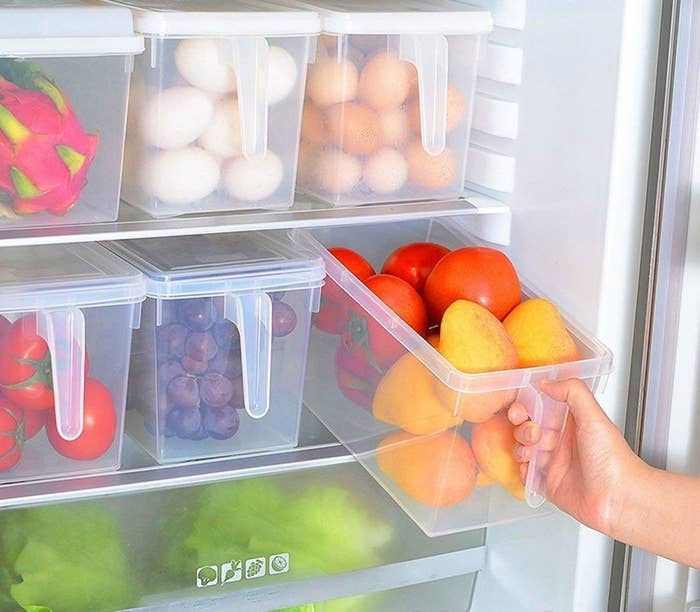 A fridge with 6 plastic storage containers with handle containing fruits and vegetables