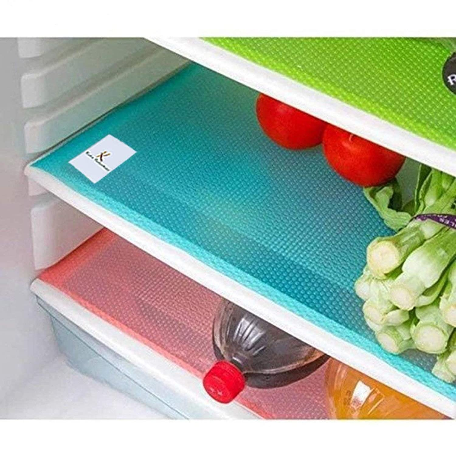 Red, blue and green mats in fridge with vegetables and beverages on top of them