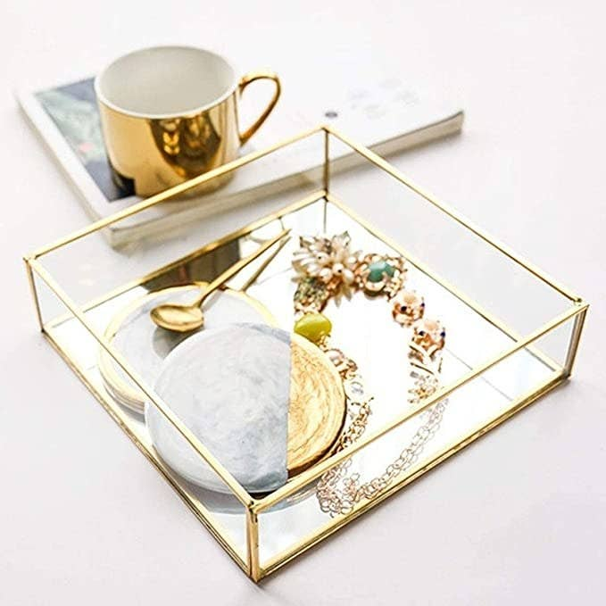 A transparent square-shaped tray with golden edges holding jewellery and other knickknacks