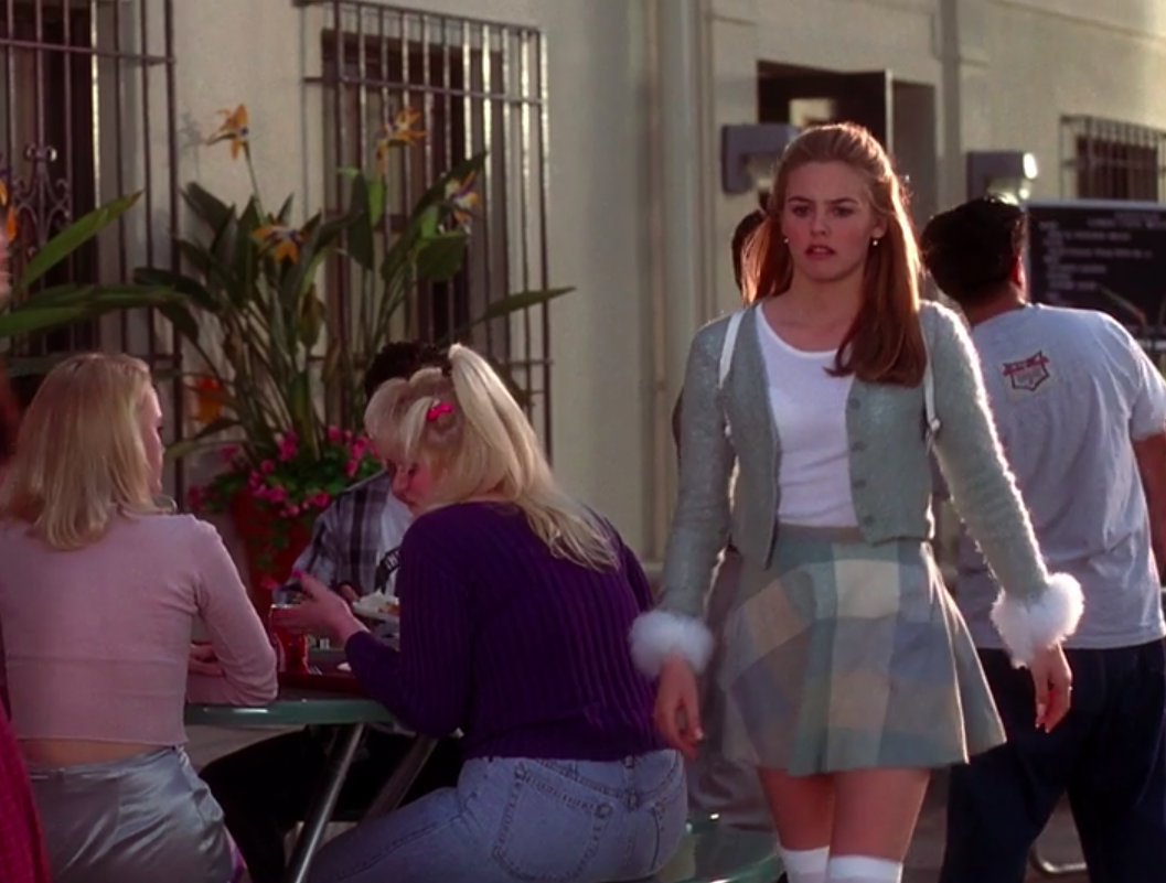 Cher wearing thigh-high socks, a mini skirt, a shirt, a cardigan with fluffy cuffs, and a backpack