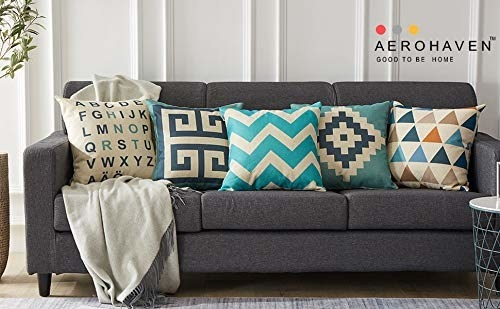 A set of 5 cushions with geometric prints in white, blue, teal, and orange. They're arranged on a dark grey sofa.