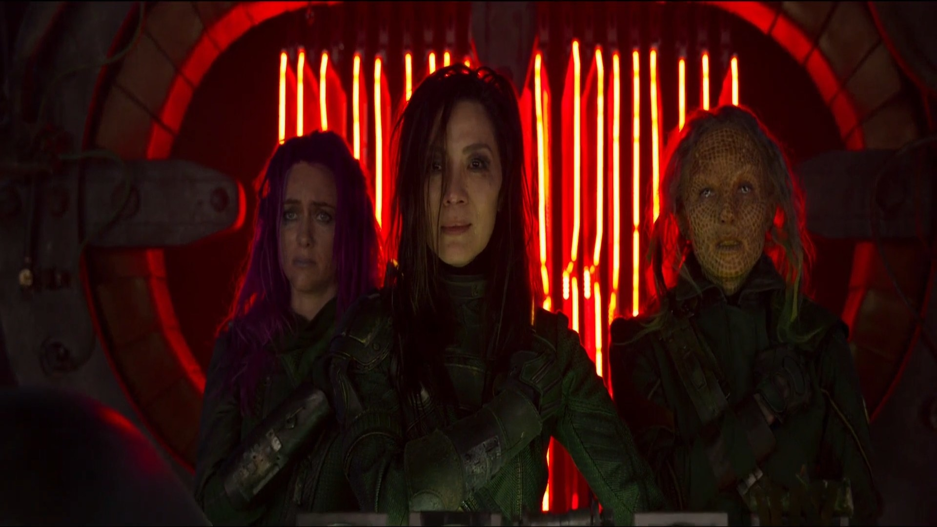 Three women, one of them alien, making a gesture of touching their hearts with their right hands.