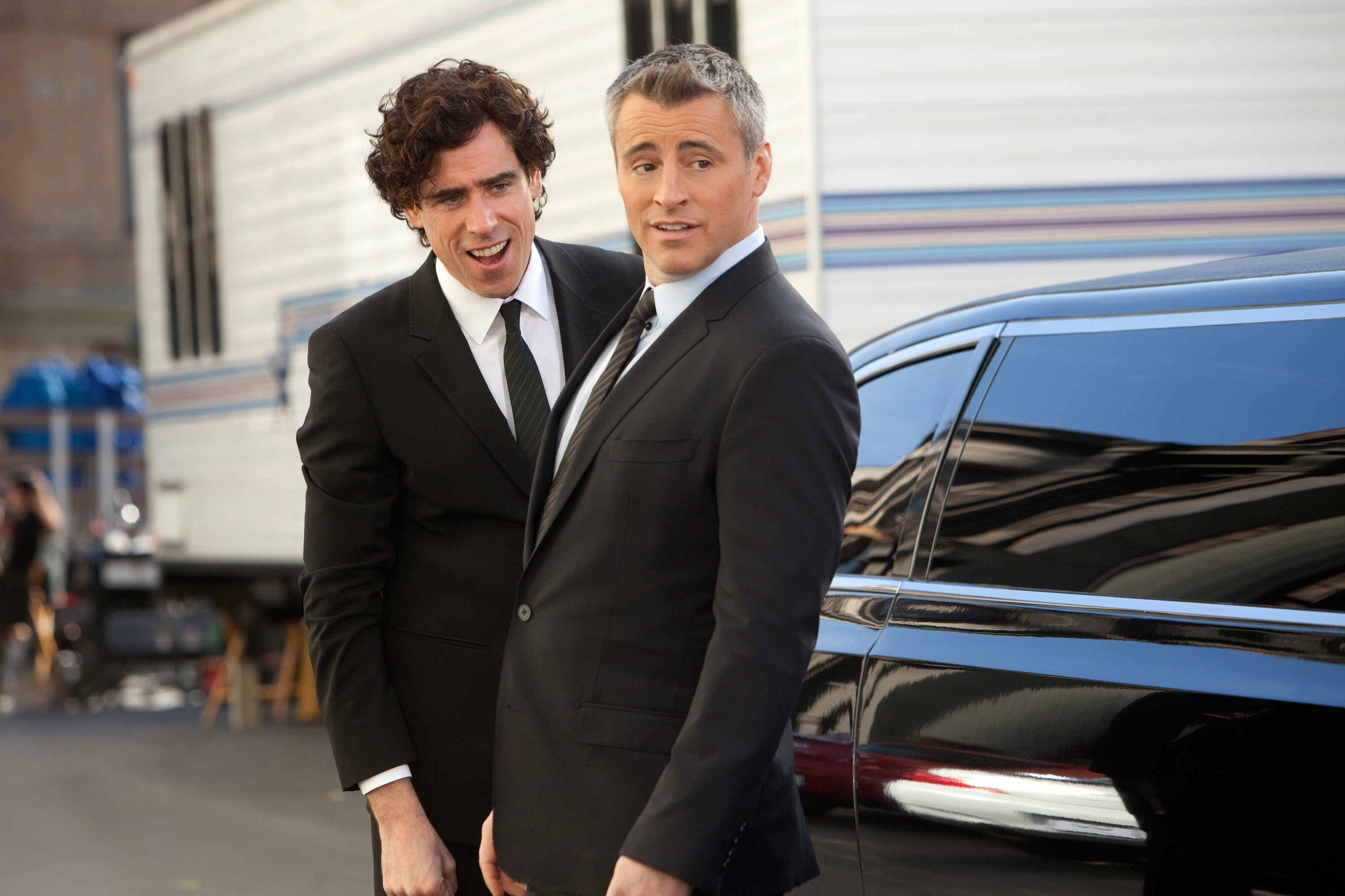 """Stephen Mangan and Matt LeBlanc wearing suits and standing outside of a limo as Sean and Matt on """"Episodes"""""""