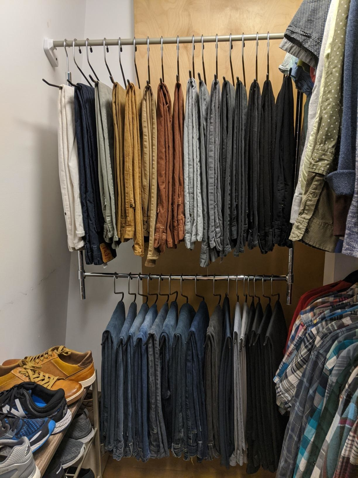 reviewer's closet with pants hung on the top and bottom of the adjustable closet rod