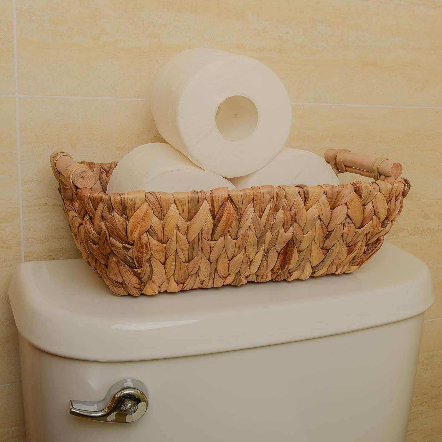 a woven hyacinth basket with toilet paper rolls inside of it sitting atop a toilet