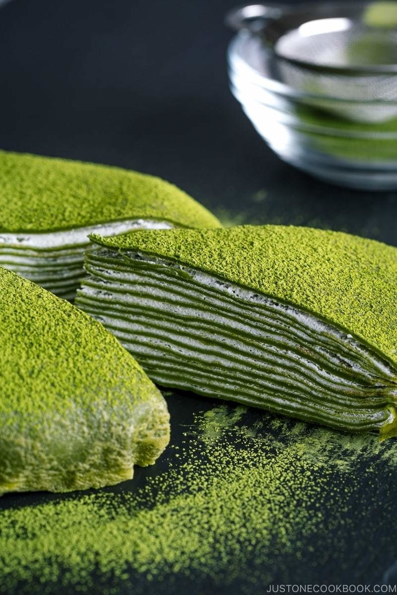 Dusted matcha mille crepe cake with a protruding slice showing the creme filling.