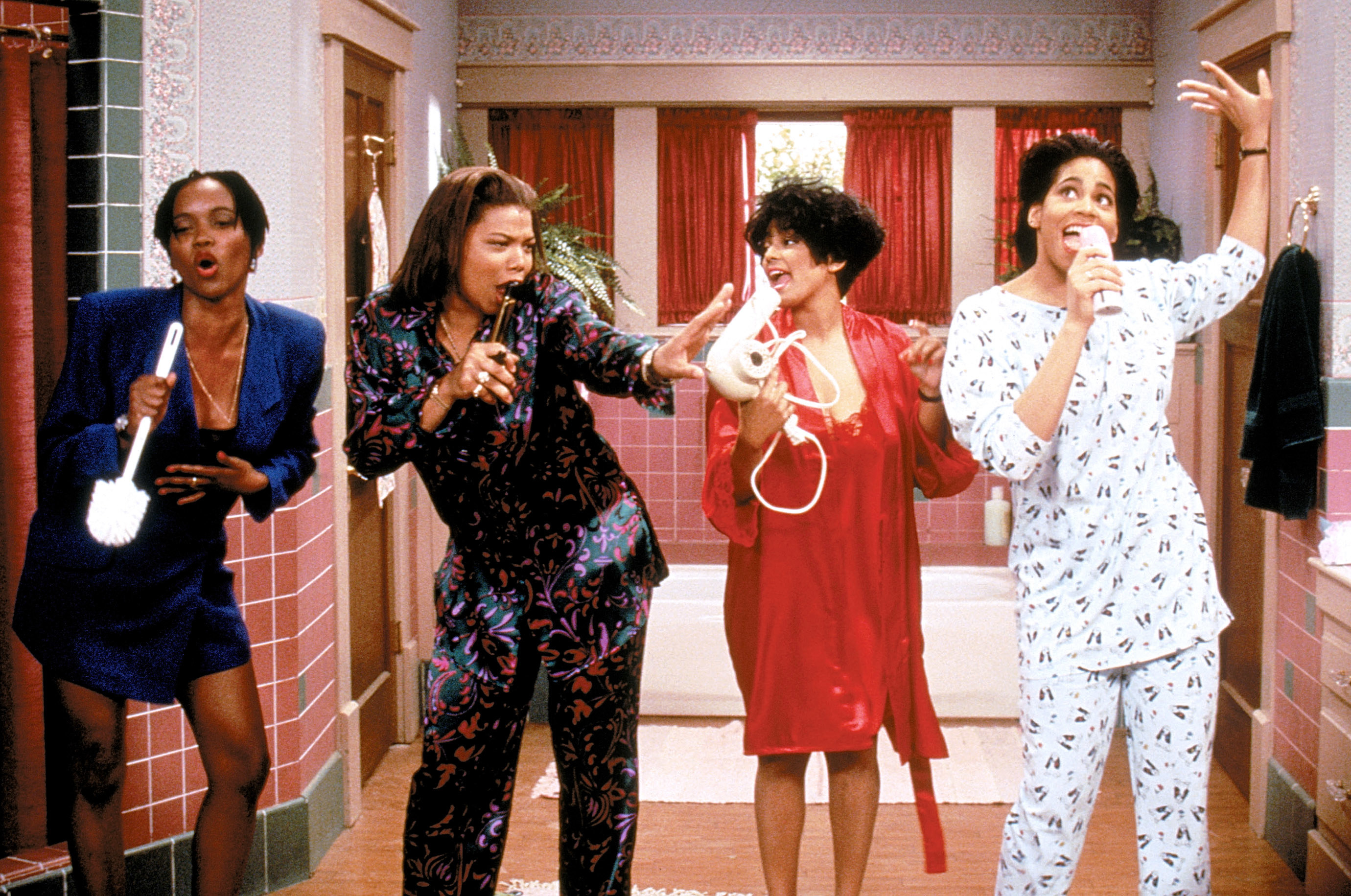 """Erika Alexander, Queen Latifah, Kim Fields, and Kim Coles singing into hair brushes, blow dryers, and other beauty and bathroom products asMax,Khadijah,Regine, andSynclaire on """"Living Single"""""""
