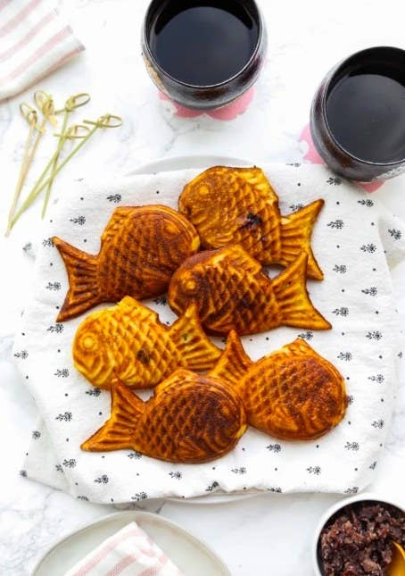 Group of Taiyaki pastries laying on a patterned cloth on top of a plate.