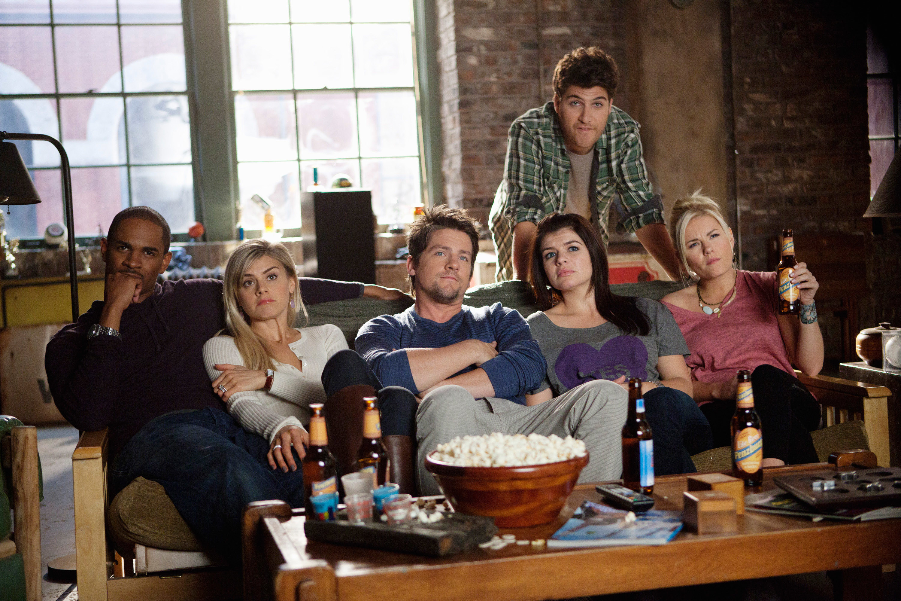 """Damon Wayans Jr., Eliza Coupe, Zachary Knighton, Casey Wilson, Adam Pally, and Elisha Cuthbert sitting on the couch drinking beer as Brad, Jane, Dave, Penny, Max, and Alex on """"Happy Endings"""""""