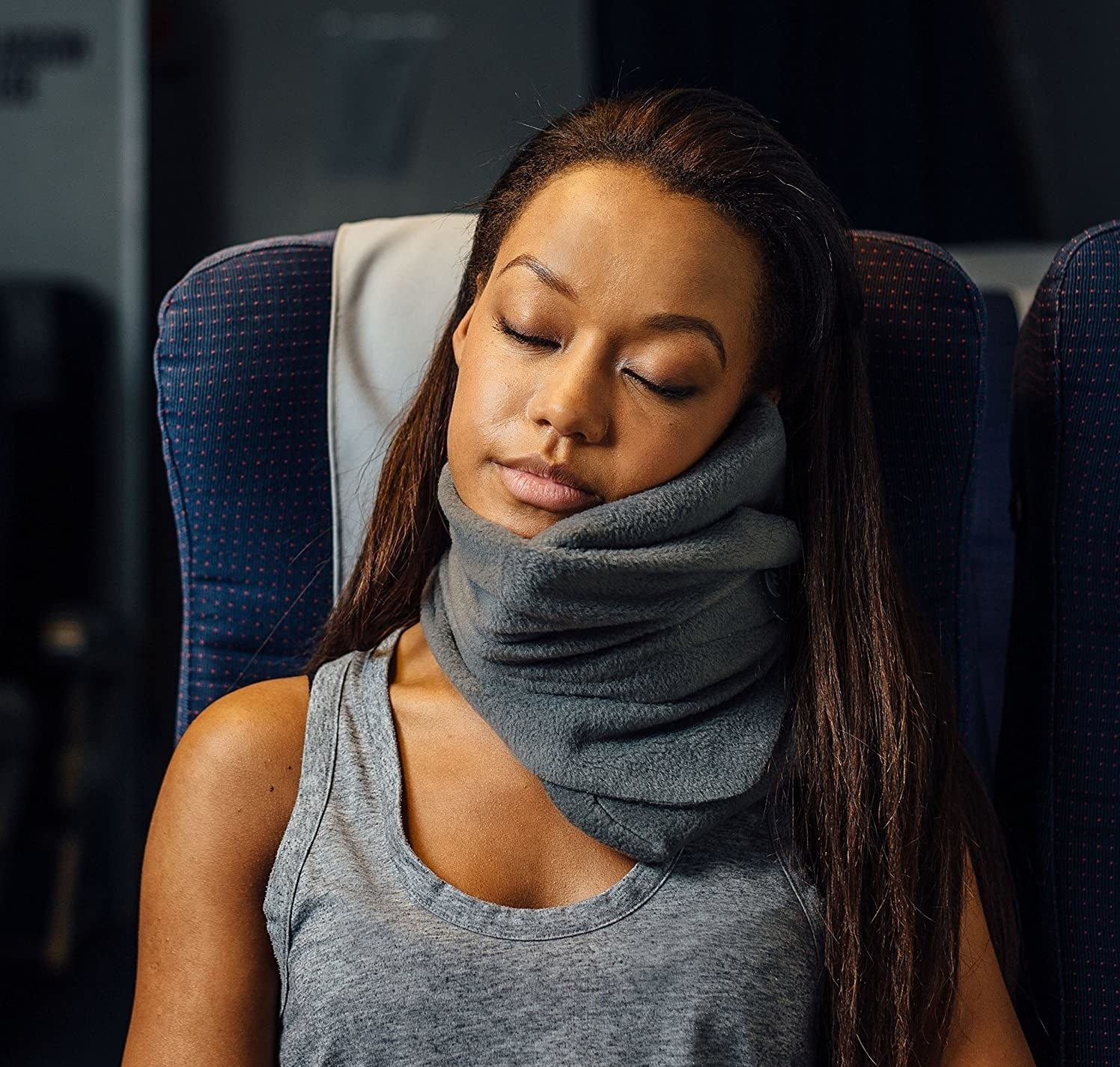 model wearing a gray trtl pillow while sleeping on a plane