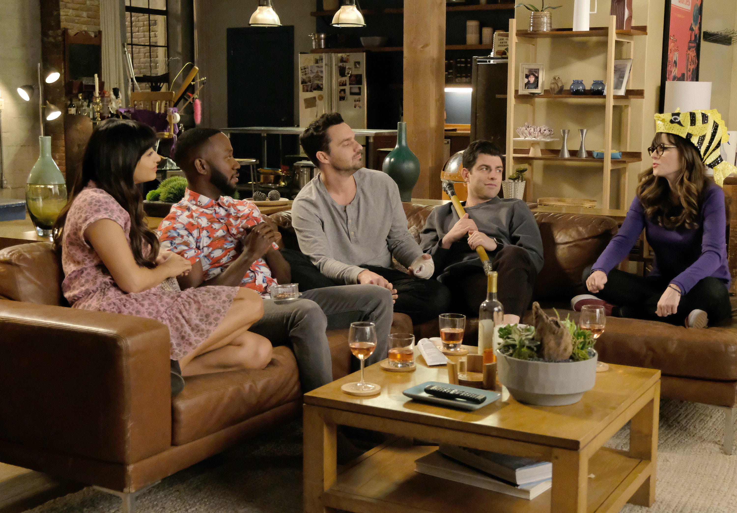 """Hannah Simone, Lamorne Morris, Jake Johnson, Max Greenfield, and Zooey Deschanel sitting on the couch with glasses of wine in front of them as Cece, Winston, Nick, Schmidt, and Jess on """"New Girl"""""""