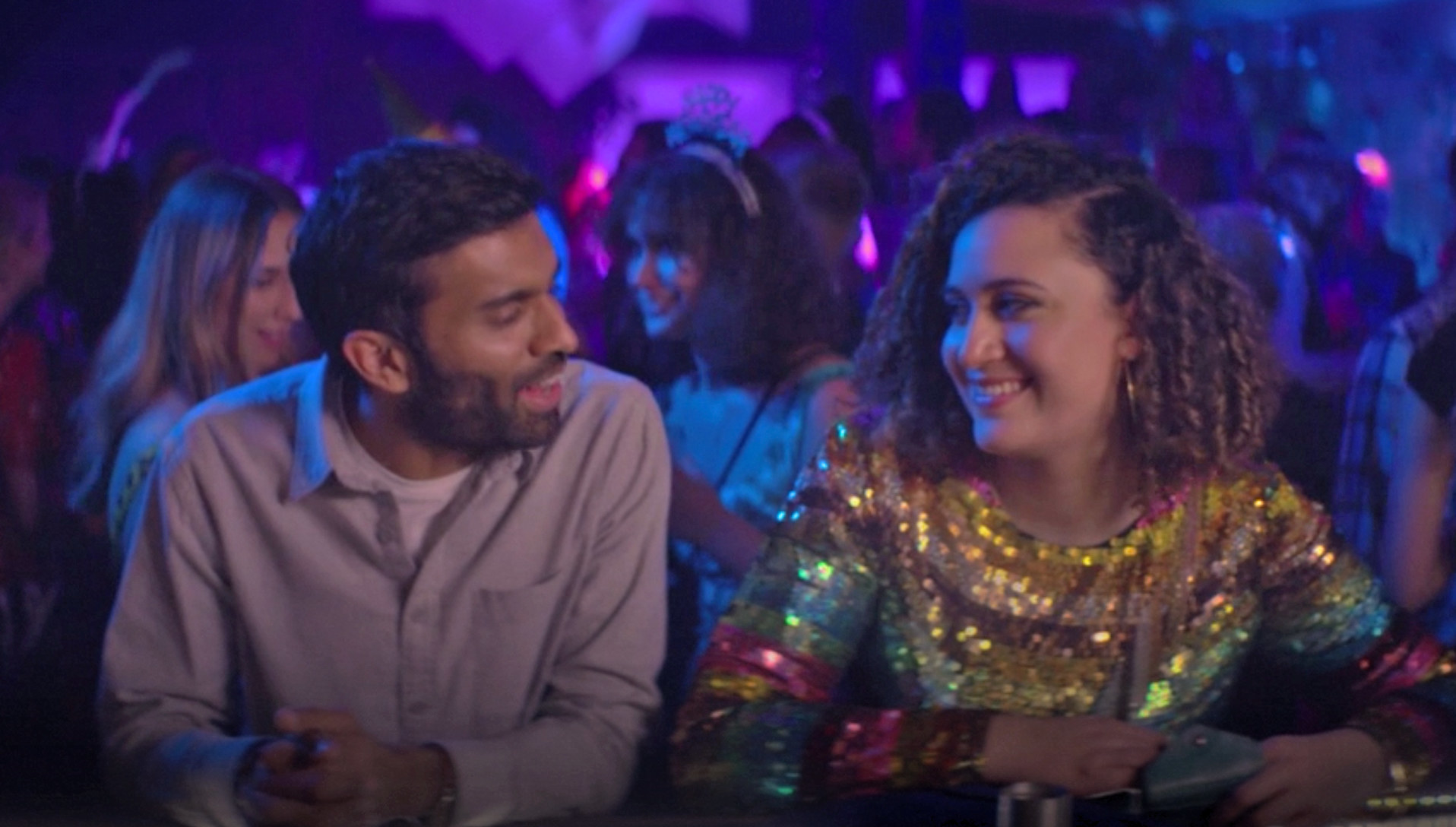"""Nikesh Patel and Rose Matafeo sitting at a bar as Tom and Jessie on """"Starstruck"""""""