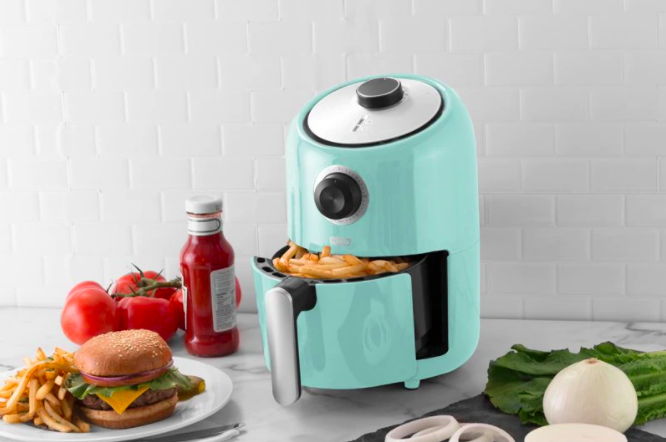 A brightly coloured air fryer filled with fresh french fries