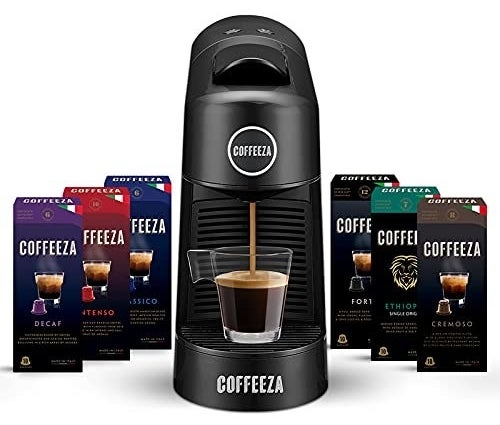 A Coffeeza Finero machine next to multiple coffee bean capsule packs such as Decaf, Classico, and Cremoso, among others
