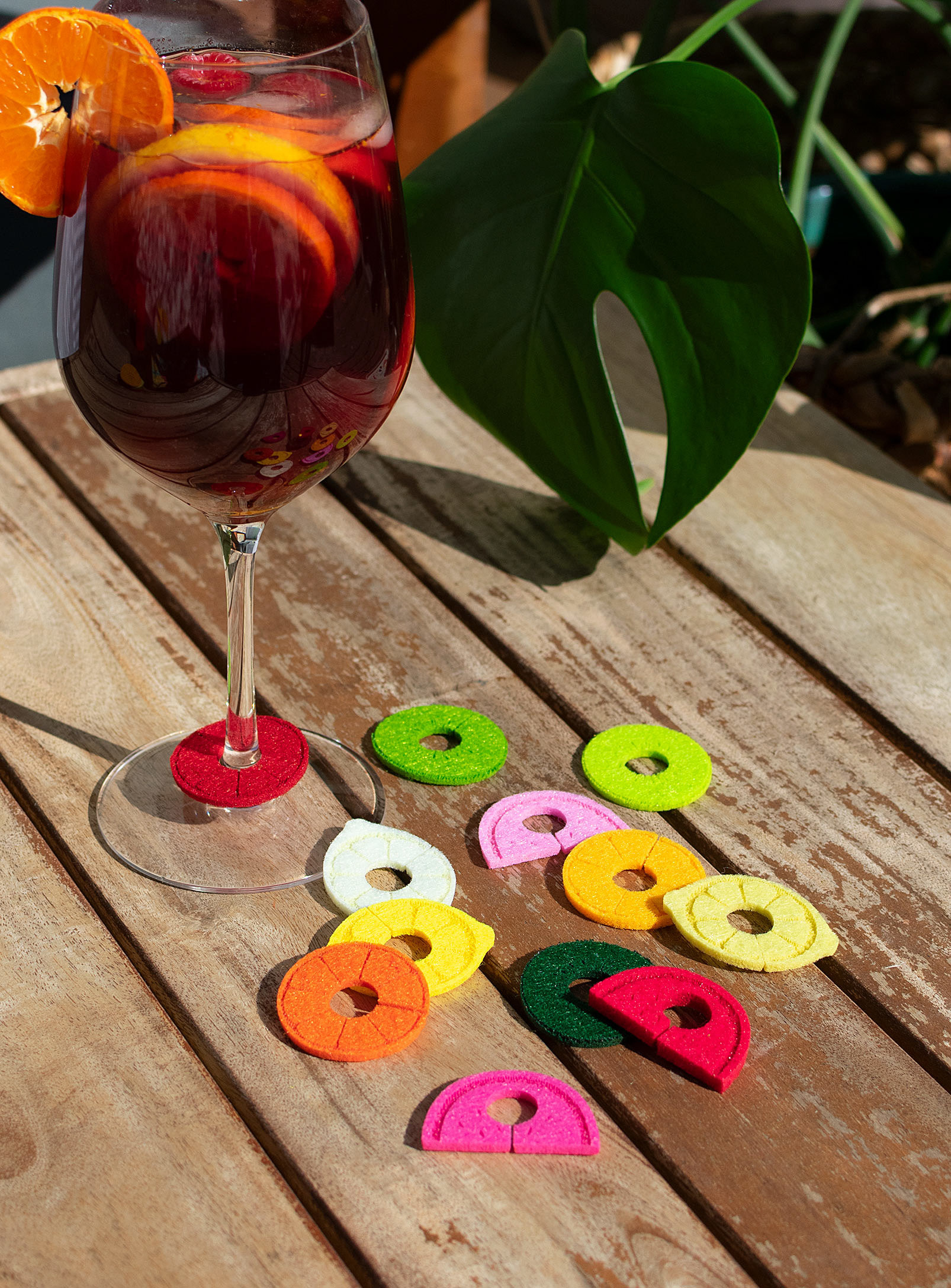 A set of felt fruit-shaped drink markers next to a full wine glass