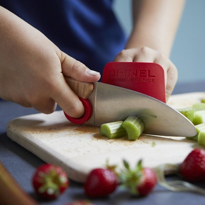 A close up of a person using the chef's knife to slice celery; the finger guard is protecting their hand from injury