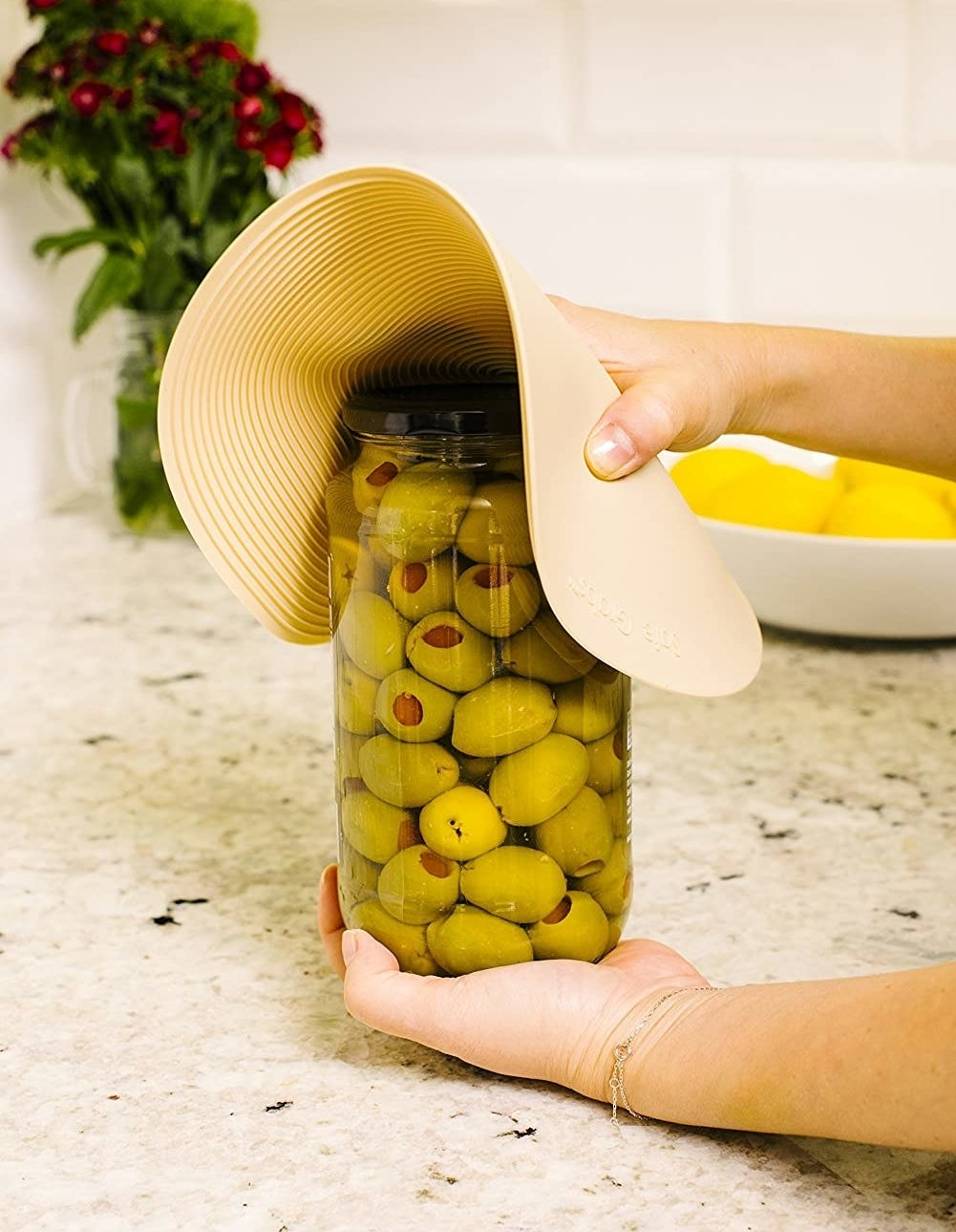 Someone using the silicone mat to open a jar of olives