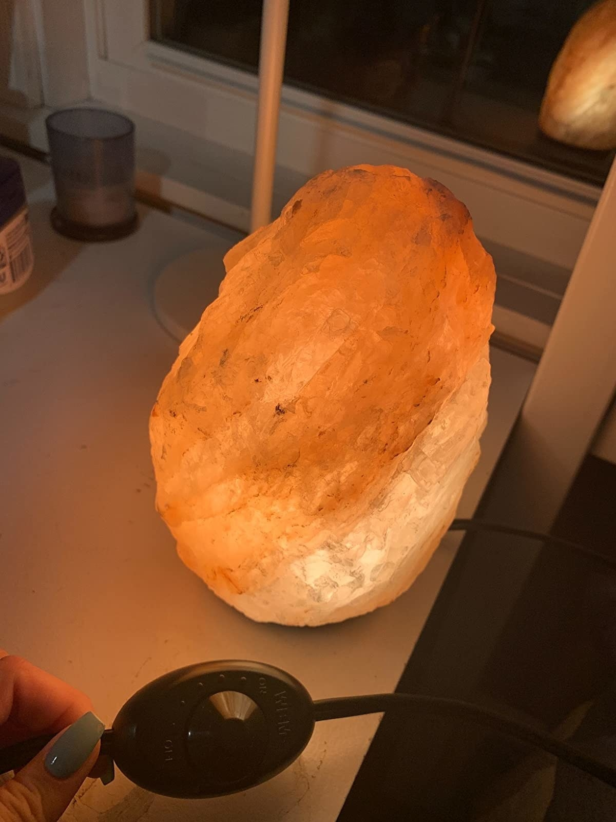 Reviewer photo of the salt lamp while they hold the switch showing the dimmer option