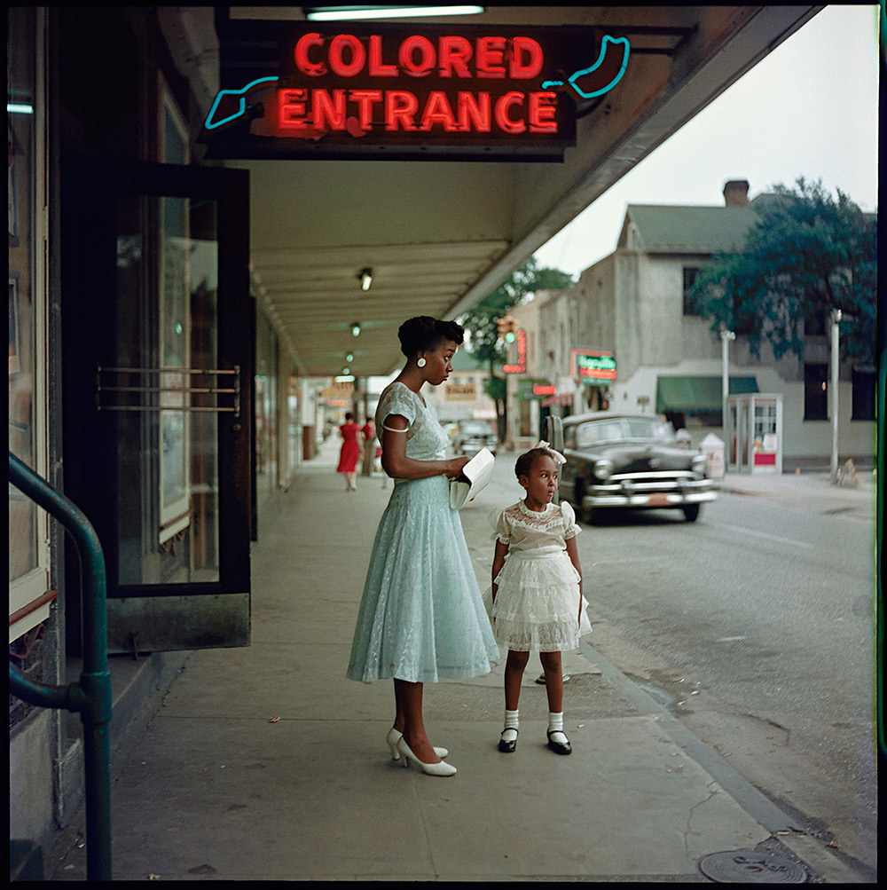 """A mother and child in dresses stand under a """"colored entrance"""" sign"""