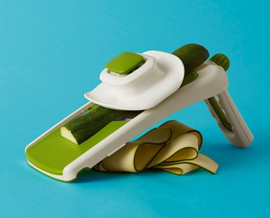 A collapsible mandoline with a half-shaved zucchini on tp